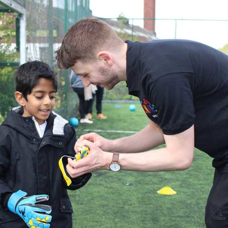 Young boy being helped by an instructor to put his goalie gloves on