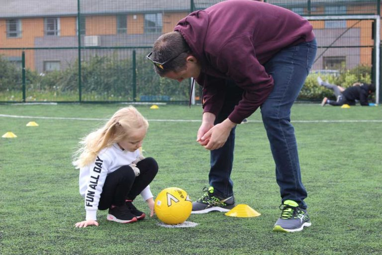 Young girl and instructor talking about football