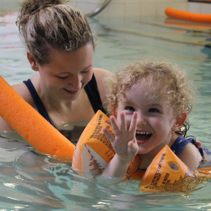 Physioterapist in Hydrotherapy pool with young child